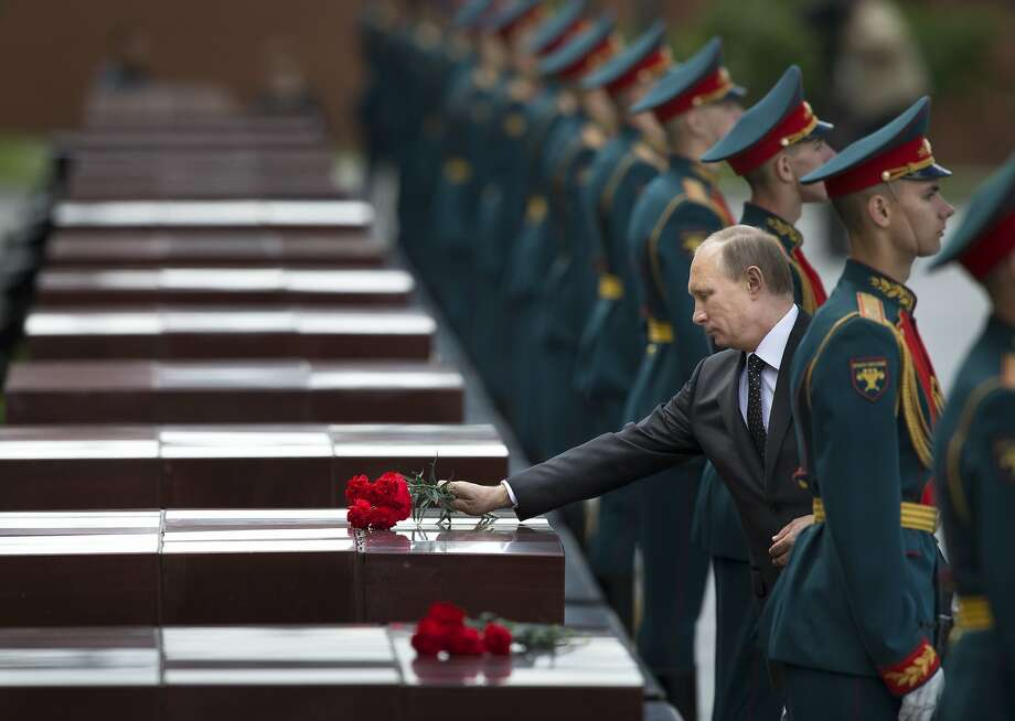 Russian Vladimir Putin, second right, takes part in a wreath laying ceremony at the Tomb of the Unknown Soldier outside Moscow's Kremlin Wall, in Moscow, Russia, Sunday, June 22, 2014,  to mark the 73rd anniversary of the Nazi invasion of the Soviet Union. (AP Photo/Alexander Zemlianichenko) Photo: Alexander Zemlianichenko, Associated Press