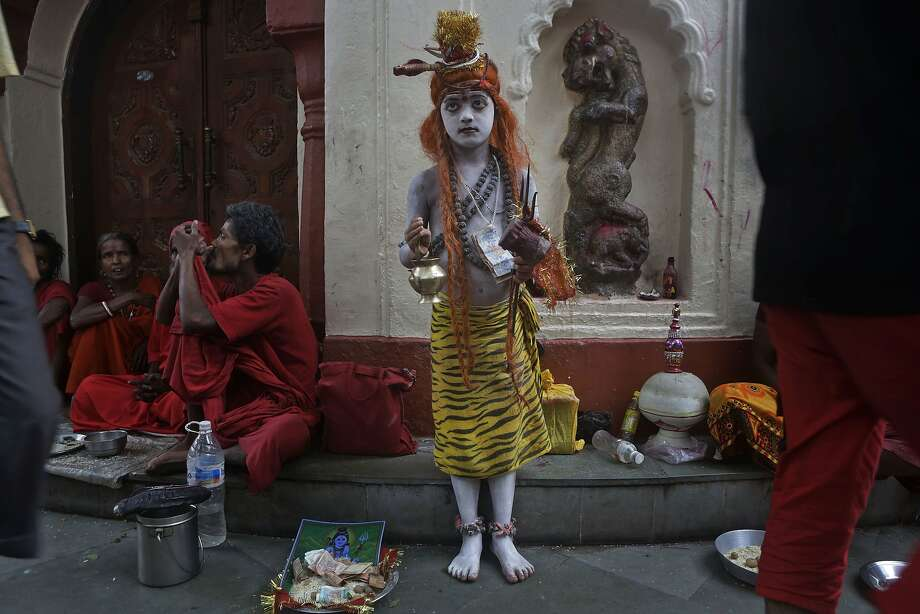 An Indian boy stands dressed like Hindu god Shiva to attract alms from devotees as a man smokes marijuana, left, during the Ambubasi festival at the Kamakhya Hindu temple in Gauhati, India, Sunday, June 22, 2014. The annual festival where hundreds of holy men from an esoteric form of Hinduism, gather to perform rituals at the temple began Sunday. (AP Photo/Anupam Nath) Photo: Anupam Nath, Associated Press