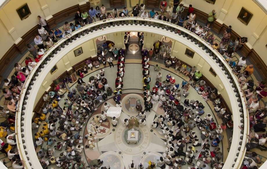 Worshippers gather at the state Capitol during a Corpus Christi procession that started at St. Mary's Cathedral for the Feast of Corpus Christi on Sunday June 22, 2014, in Austin, Texas. (AP Photo/Austin American-Statesman, Jay Janner)  AUSTIN CHRONICLE OUT, COMMUNITY IMPACT OUT, MAGS OUT; NO SALES; INTERNET AND TV MUST CREDIT PHOTOGRAPHER AND STATESMAN.COM Photo: Jay Janner, Associated Press