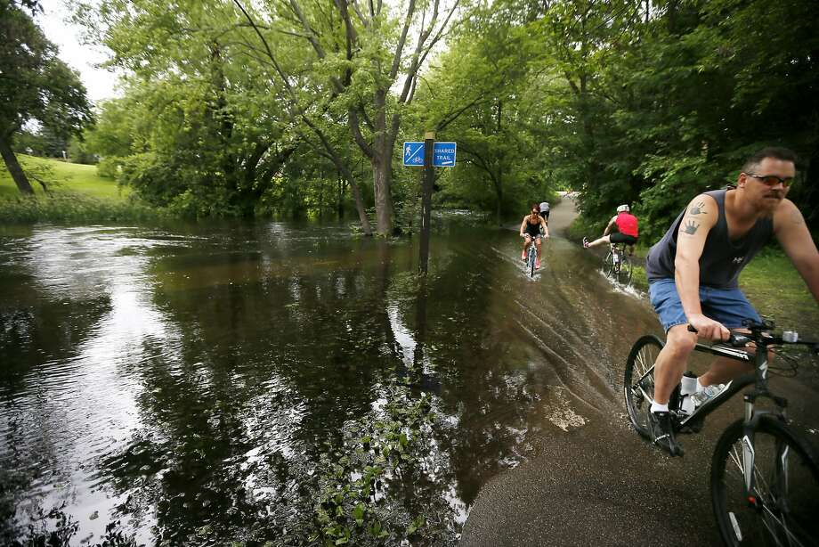 High water flooded the walking and bike paths along Minnehaha Creek on Sunday, June 22, 2014, in Minneapolis. (AP Photo/The Star Tribune, Jerry Holt) Photo: Jerry Holt, Associated Press