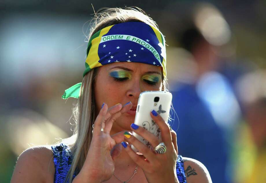 SAO PAULO, BRAZIL - JUNE 12:  A Brazil fan uses a mobile phone before the Opening Ceremony of the 2014 FIFA World Cup Brazil prior to the Group A match between Brazil and Croatia at Arena de Sao Paulo on June 12, 2014 in Sao Paulo, Brazil. Photo: Adam Pretty, Getty Images / 2014 Getty Images