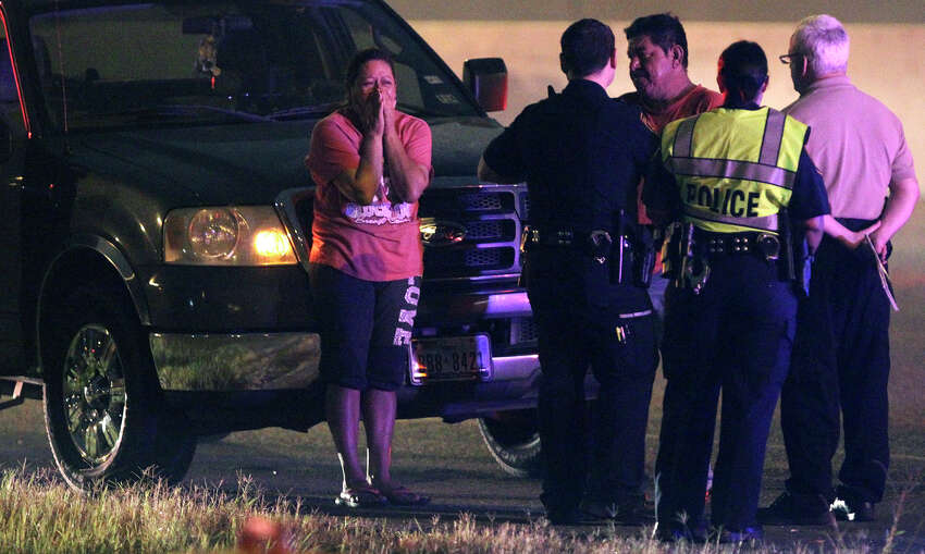 A woman appears distraught (center) while San Antonio police investigate the scene of a fatal car crash that took place about 3:30 a.m. Monday, June 23, 2014, on northbound U.S. 281 near Nakoma. According to local television reports, police said the driver of the vehicle slammed into a concrete pillar and the car caught fire. Northbound 281 was reduced to one lane of traffic while the accident was being cleared.