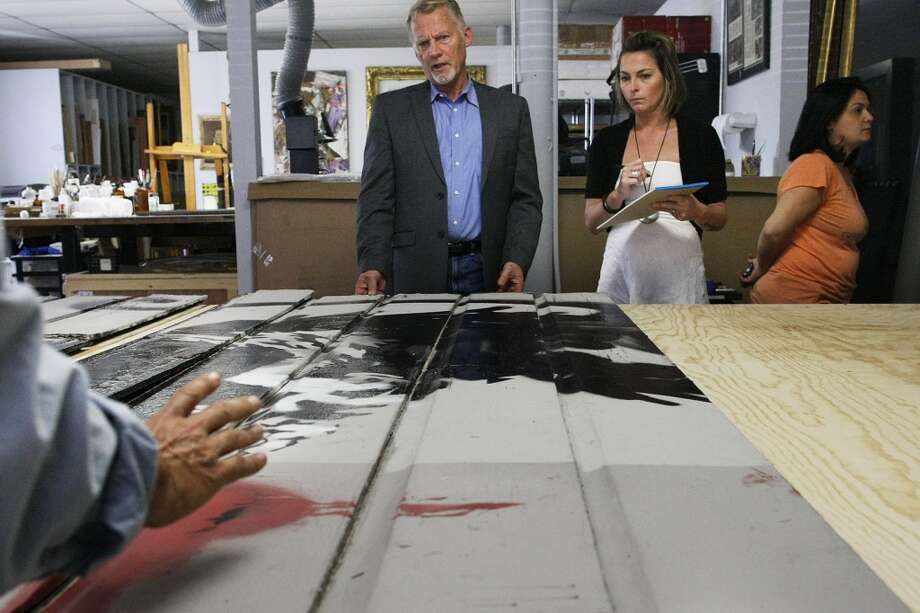 Left to right, Scott Haskins, Francesca Ruggeri and Oriana Montemurro examine the piece by Banksy. Photo: James Tensuan, The Chronicle