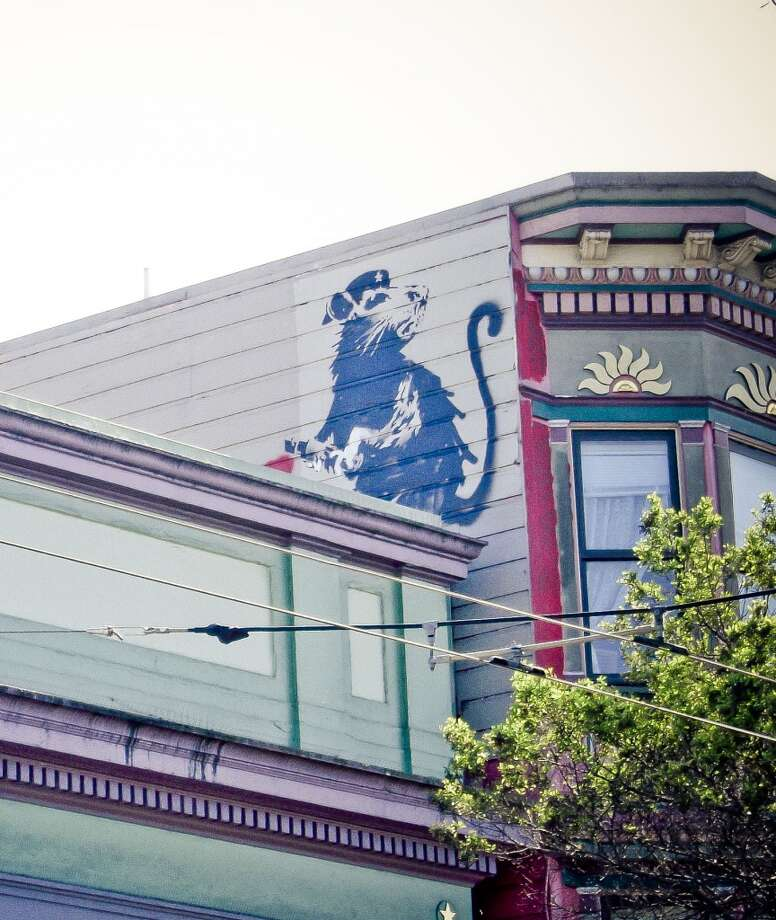 A painting of a rat clutching a magic marker by the anonymous street artist Banksy is shown before its removal from the side of the Red Victorian inn at 1665 Haight St. in San Francisco. Banksy left the graffiti there in 2010. Photo: Brian Greif