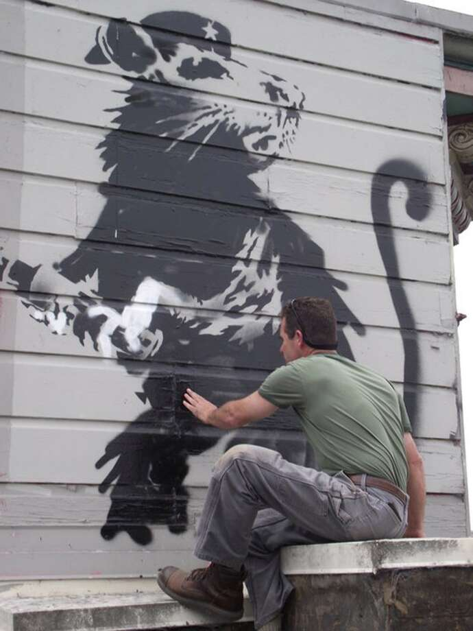 A worker prepares to remove a painting of a rat clutching a magic marker by the anonymous street artist Banksy, who left the graffiti in 2010 on the side of the Red Victorian inn at 1665 Haight St. in San Francisco. Art enthusiast Brian Greif is now seeking to restore and publicly display the piece. Photo: Brian Greif