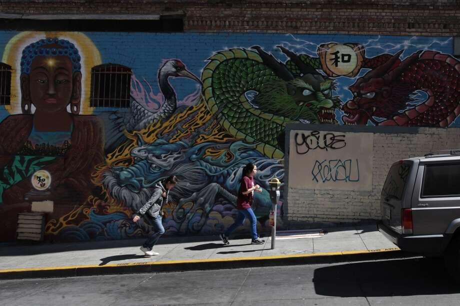 The Chinatown Banksy is no more. Two women run by the mural that covers it on Thursday, June 19, 2014. Photo: James Tensuan, The Chronicle