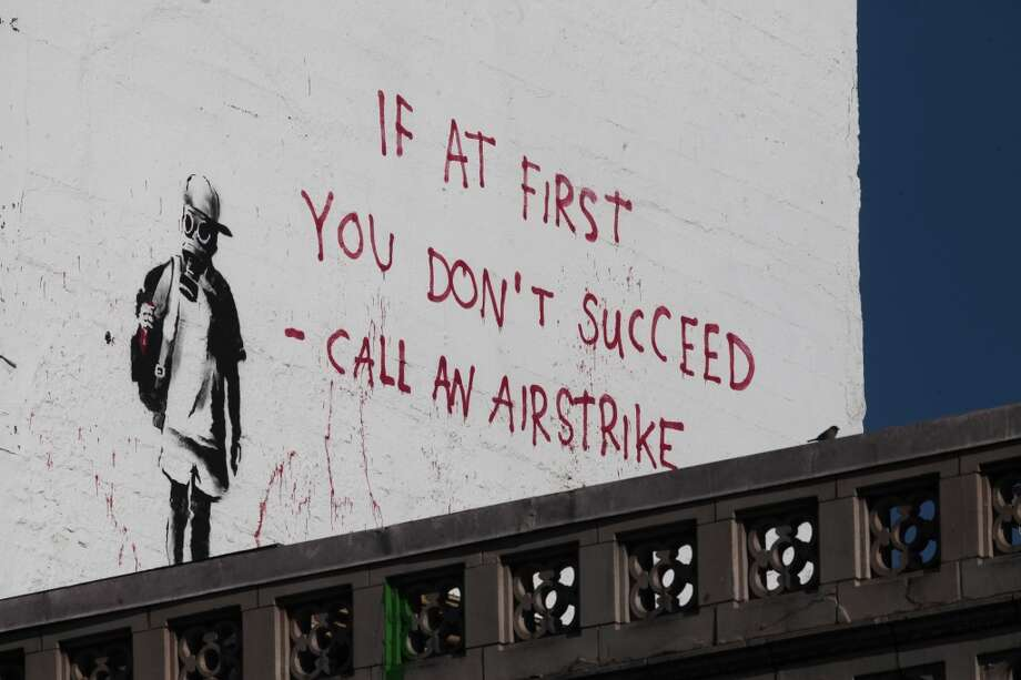 A Banksy piece looms over the corner of Columbus Avenue and Broadway Street in San Francisco on June 19, 2014. Photo: James Tensuan, The Chronicle