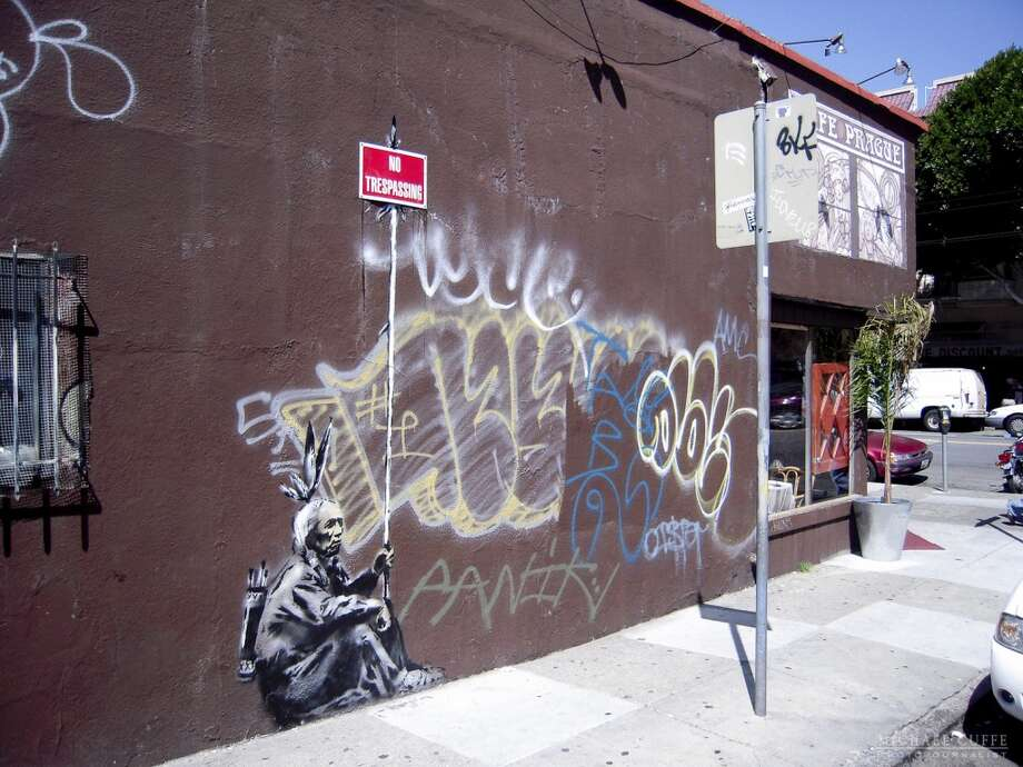 "This Banksy piece depicting an American Indian holding a ""No Trespassing"" sign was drawn at 2140 Mission St. in San Francisco. Photo: Photograph By Michael Cuffe"