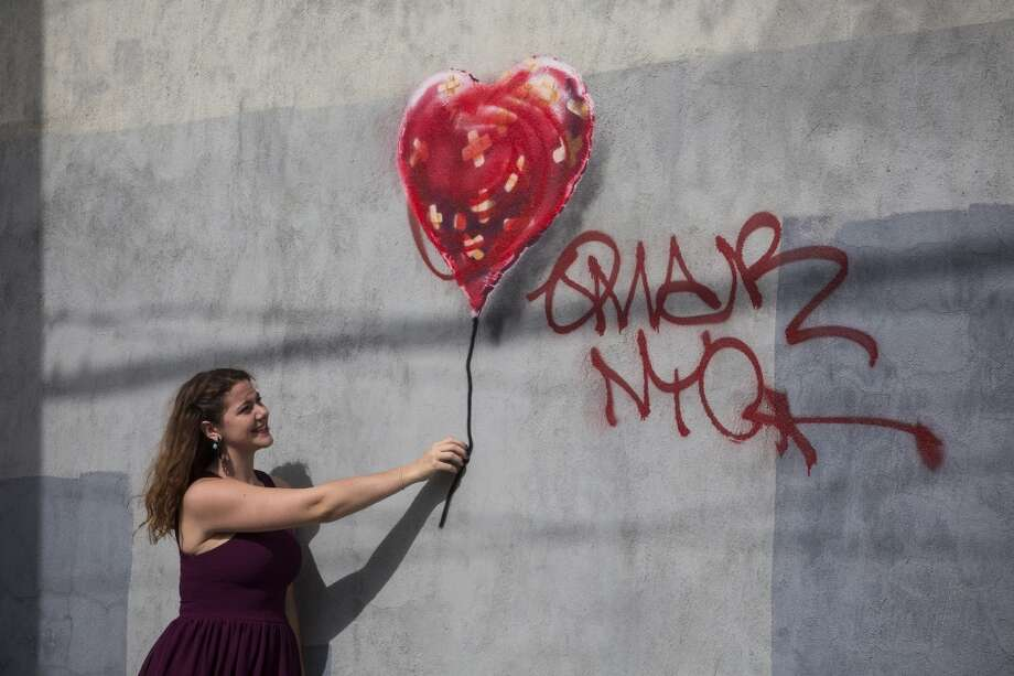 Banksy left his mark on New York City in 2013. A woman poses with a piece of street art, which depicts a heart-shaped balloon covered in bandages on Oct. 7, 2013 in the Red Hook neighborhood of Brooklyn. The piece was defaced with red spray paint shortly after completion. Photo: Andrew Burton, Getty Images