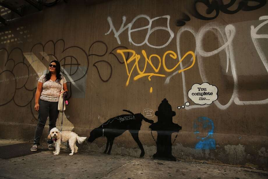 Also in New York, Christina Ng poses in front of a new Bansky work with her dog Cece on Oct. 3, 2013. Photo: Spencer Platt, Getty Images