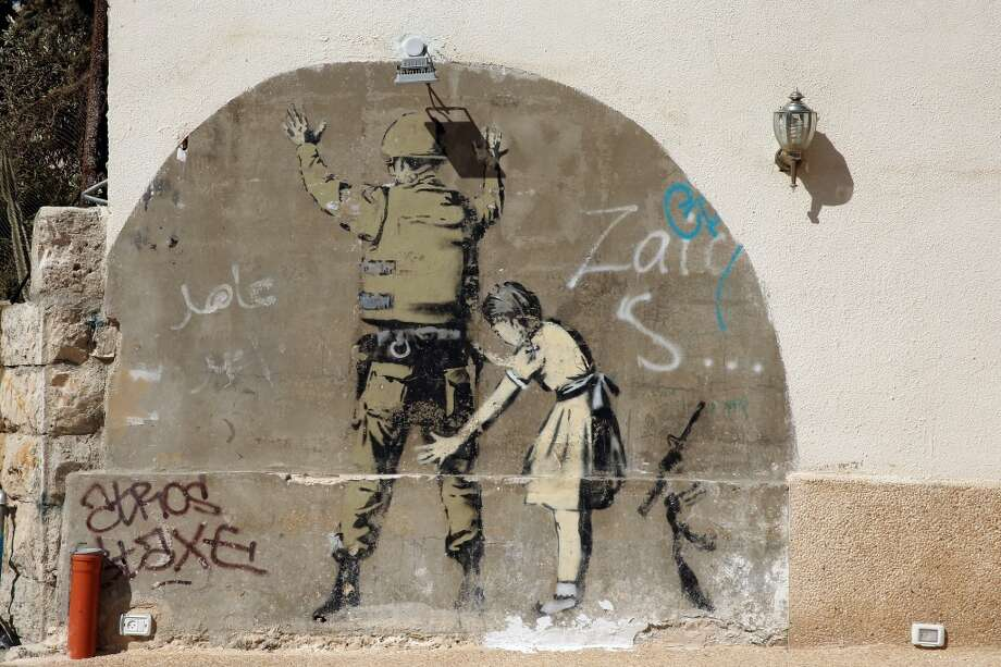 General views of a Banksy wall painting near Bethlehem on June 16, 2013, in central West Bank. Photo: Ian Walton, Getty Images