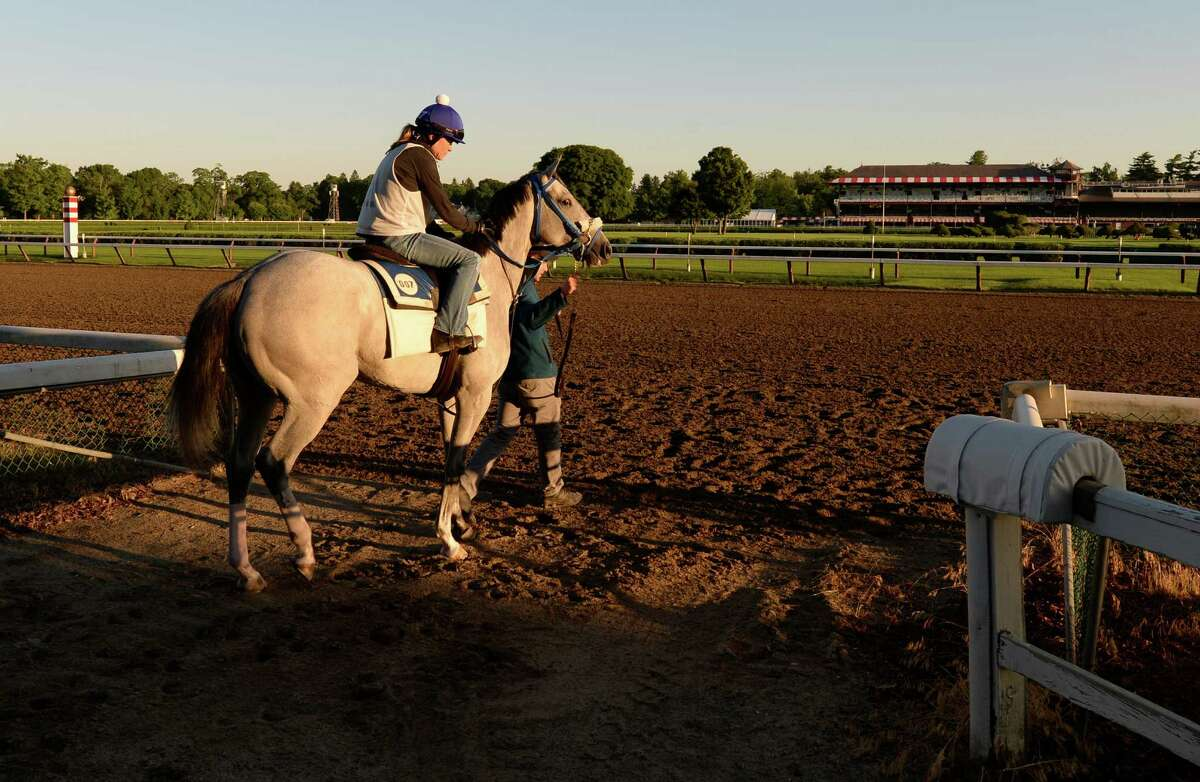 Hot And Spicy, with exercise rider Katie Schmidt aboard, is lead to the main track by assistant trainer Ryan Bond at Saratoga Race Course on the opening day of the main track for training Monday morning, June 23, 2014, in Saratoga Springs, N.Y. The 151st race meeting at the historic track will begin on July 18th and run through Labor Day. (Skip Dickstein/Times Union)