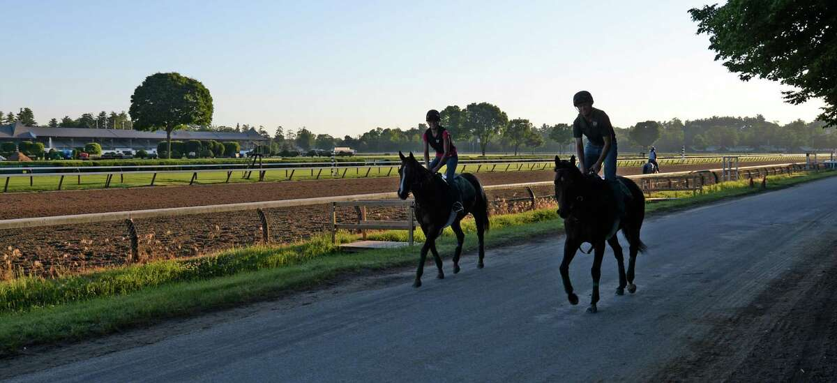 Trainer Arch Kingsley aboard Central Banker, right, and Grace LaBarre aboard Southbound Swinger, left, jog down the lane at Saratoga Race Course on the opening day of the main track for training Monday morning, June 23, 2014, in Saratoga Springs, N.Y. The 151st race meeting at the historic track will begin on July 18th and run through Labor Day. (Skip Dickstein/Times Union)