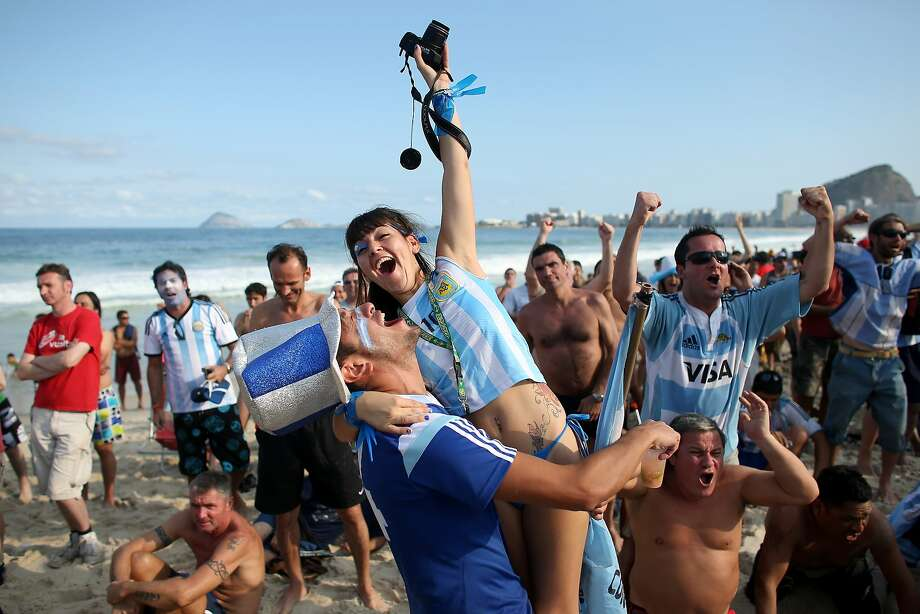 Argentine soccer team fans react to their team scoring against the Iran team as they watch on the screen setup at the Word Cup FIFA Fan Fest during on Copacabana beach June 21, 2014 in Rio de Janeiro, Brazil. Argentina won the match 1-0. Photo: Joe Raedle, Getty Images