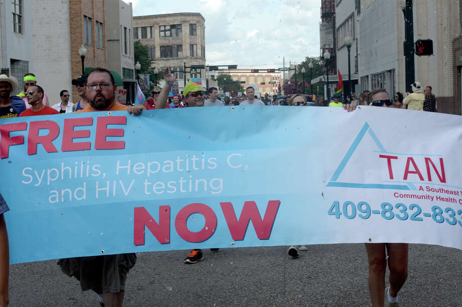 Supporters hold signs while walking along Orleans Street during Beaumont's first Pride Parade on Saturday. 