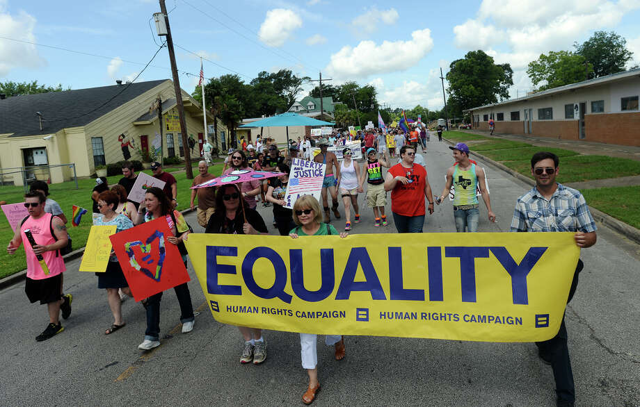 Marchers carry signs calling for equality and love down Broadway Street during the Pride Walk on Saturday. Beaumont's first ever gay pride event was held on Saturday. The day began with a walk from the intersection of Martin Luther King Parkway and Broadway into the 500 and 600 block of Orleans Street in downtown Beaumont.