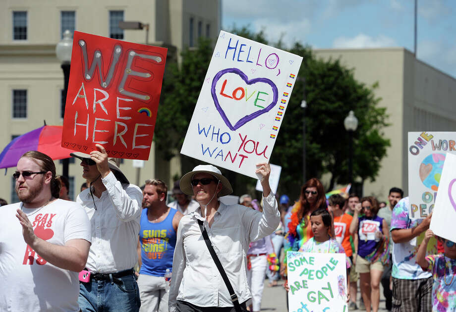 Marchers carry signs down Broadway Street during Saturday's Pride Walk. Beaumont's first ever gay pride event was held on Saturday. The day began with a walk from the intersection of Martin Luther King Parkway and Broadway into the 500 and 600 block of Orleans Street in downtown Beaumont. Photo taken Saturday 6/21/14 Jake Daniels/@JakeD_in_SETX Photo: Jake Daniels / ©2014 The Beaumont Enterprise/Jake Daniels