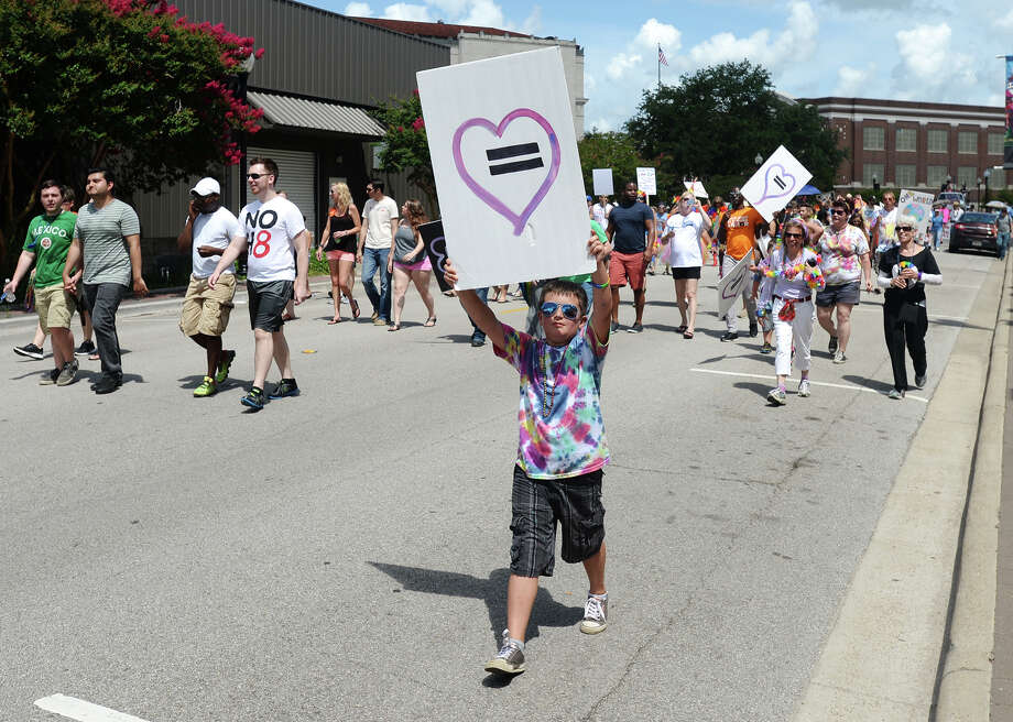 A young marcher carries an equality sign down Orleans Street during Saturday's Pride Walk. Beaumont's first ever gay pride event was held on Saturday. The day began with a walk from the intersection of Martin Luther King Parkway and Broadway into the 500 and 600 block of Orleans Street in downtown Beaumont.