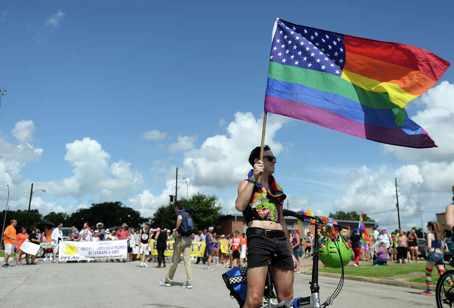 Dustin Lydic holds a star spangled rainbow flag as he and others await the beginning of Saturday's Pride Walk down Boardway Street. Beaumont's first ever gay pride event was held on Saturday. The day began with a walk from the intersection of Martin Luther King Parkway and Broadway into the 500 and 600 block of Orleans Street in downtown Beaumont. Photo taken Saturday 6/21/14 Jake Daniels/@JakeD_in_SETX Photo: Jake Daniels / ©2014 The Beaumont Enterprise/Jake Daniels