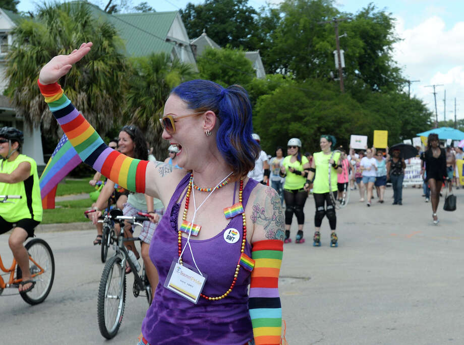 Kate James waves at onlookers as she and others participate in Saturday's Pride Walk down Broadway Street. Beaumont's first ever gay pride event was held on Saturday. The day began with a walk from the intersection of Martin Luther King Parkway and Broadway into the 500 and 600 block of Orleans Street in downtown Beaumont.
