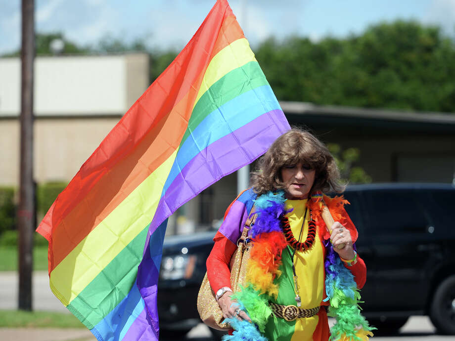 Geegee Taves carries a rainbow flag as Taves and other participants in Saturday's Pride Walk gather on Broadway Street. Beaumont's first ever gay pride event was held on Saturday. The day began with a walk from the intersection of Martin Luther King Parkway and Broadway into the 500 and 600 block of Orleans Street in downtown Beaumont.