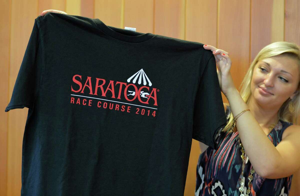 Nicole Cochetti displays a Saratoga T-shirt, one of the four giveaway items for this year's Saratoga Race Course meeting, during a press briefing about the upcoming race season Monday afternoon, June 23, 2014, at Saratoga, N.Y. The T-short will be given away August 31. (Skip Dickstein / Times Union)