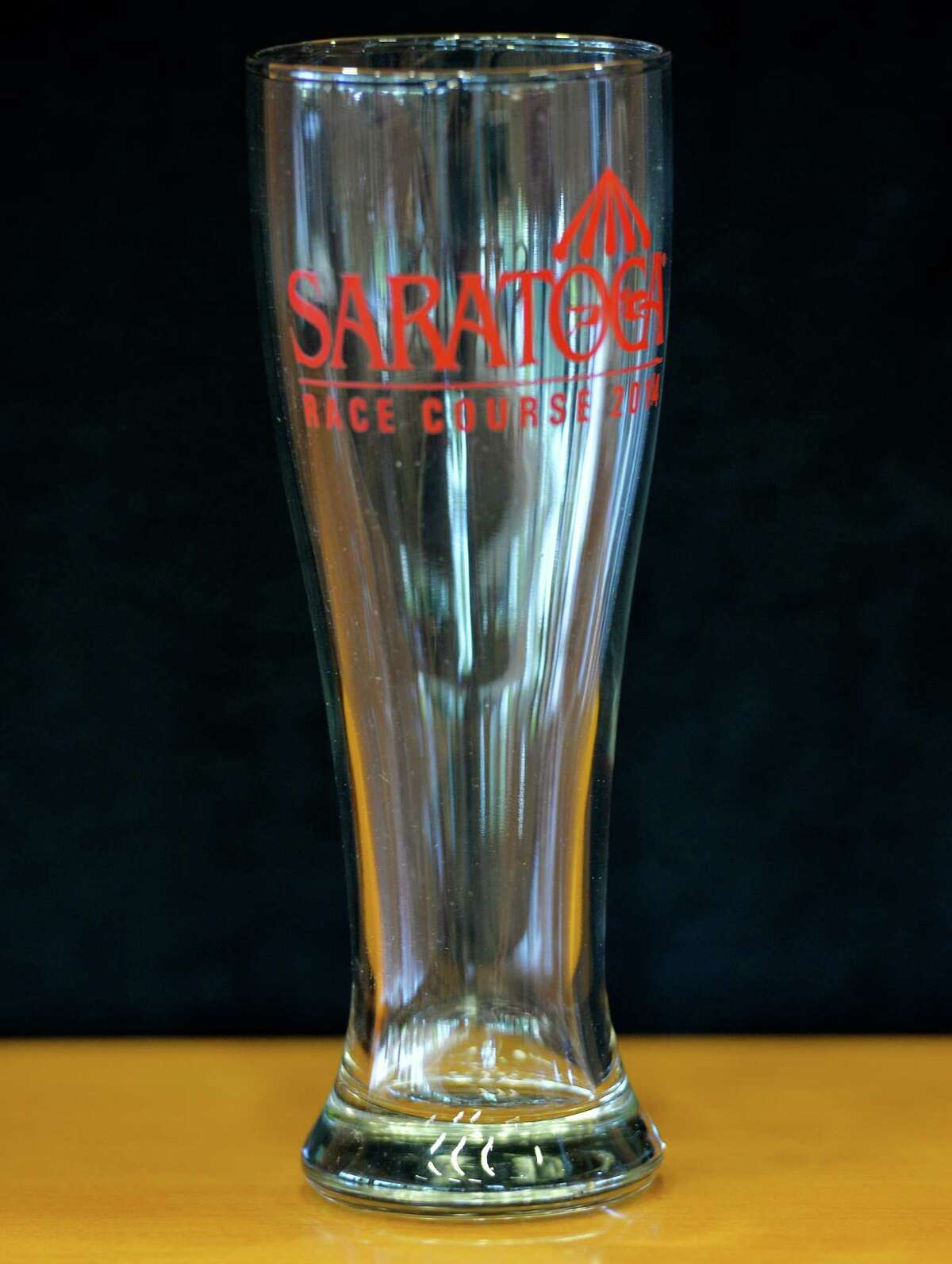 PAST GIVEAWAYS: A Saratoga pilsner glass will be one of the four giveaway items for this year's Saratoga Race Course meeting and it was displayed at a press briefing held Monday afternoon June 23, 2014 at Saratoga, N.Y. The glass will be given away July 27. (Skip Dickstein / Times Union)