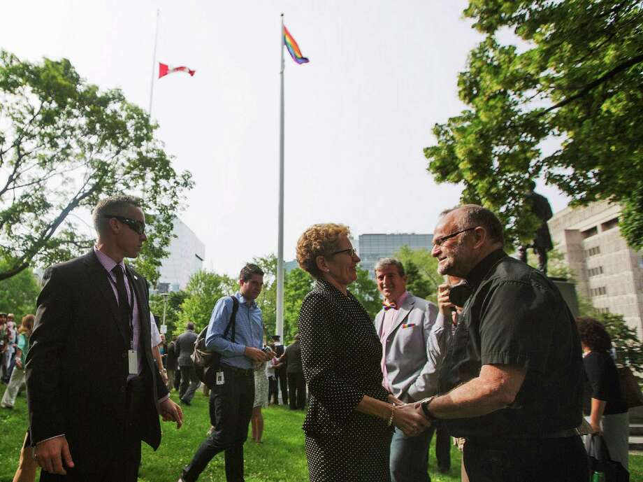 Toronto, CanadaOntario Premier Kathleen Wynne, center, speaks with gay rights activist Rev. Brent Hawkes, right, at the Pride flag raising ceremony at Queen's Park in Toronto, Canada on Monday, June, 23, 2014. Photo: Michelle Siu, Associated Press / The Canadian Press