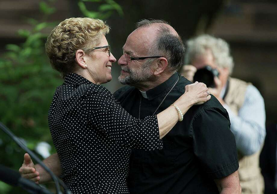 Toronto, CanadaOntario Premier Kathleen Wynne, left, embraces gay rights activist Rev. Brent Hawkes at the Pride flag raising ceremony at Queen's Park in Toronto, Canada on Monday, June, 23, 2014.   Photo: Michelle Siu, Associated Press / The Canadian Press