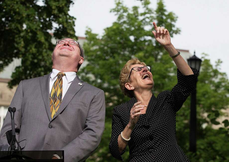 Toronto, CanadaNeill Kernohan, left, and Ontario Premier Kathleen Wynne look up during the Pride flag raising ceremony at Queen's Park in Toronto, Canada on Monday, June, 23, 2014.   Photo: Michelle Siu, Associated Press / The Canadian Press