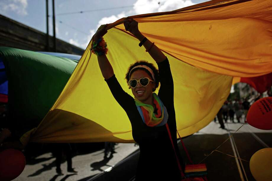 Lisbon, PortugalA woman holds up a giant rainbow flag during the Gay Pride parade celebration in Lisbon, Portugal on Saturday, June 21, 2014.  Photo: Francisco Seco, Associated Press / AP