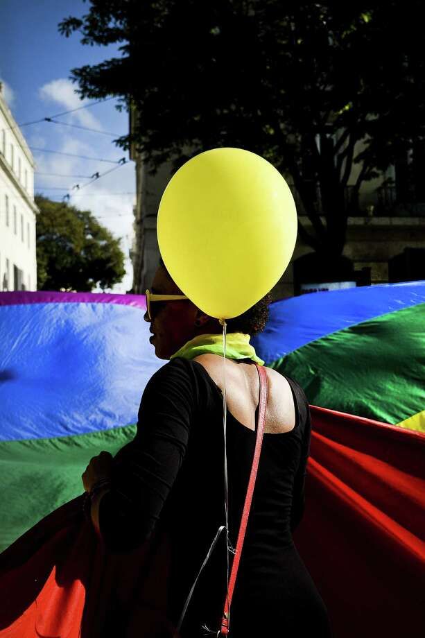 Lisbon, PortugalA woman holds a giant rainbow flag and a balloon during the Gay Pride Parade in Lisbon, Portugal on Saturday, June 21, 2014.   Photo: PATRICIA DE MELO MOREIRA, AFP/Getty Images / AFP ImageForum