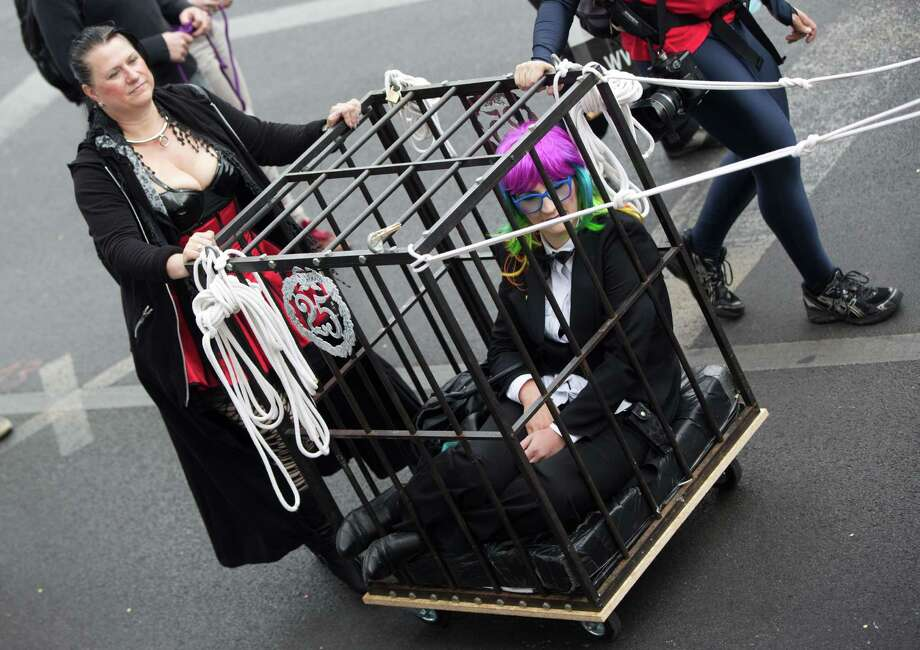 Berlin, GermanyA participant pushes a woman in a cage as they take part in the new German Christopher Street Day CSD league gay pride parade in Berlin, Germany on Saturday,  June 21, 2014. Since 35 years, the parade winds through Berlin, but this time it is divided into two pageants - the original demo and the parade of a newly formed Action Alliance.  Photo: J(div)RG CARSTENSEN, AFP/Getty Images / DPA