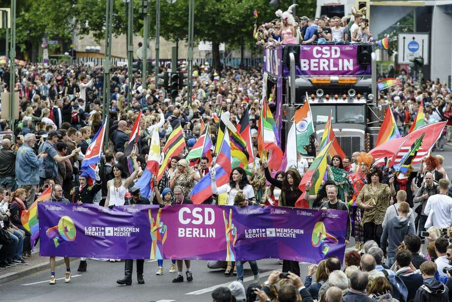 Berlin, GermanyDrag Queens wave different national flags during the Christopher Street Day (CSD) gay pride parade in front of Berlin's Memorial Church (Gedaechtniskirche) in Berlin, Germany on Saturday, June 21, 2014.  Photo: CLEMENS BILAN, AFP/Getty Images / AFP ImageForum