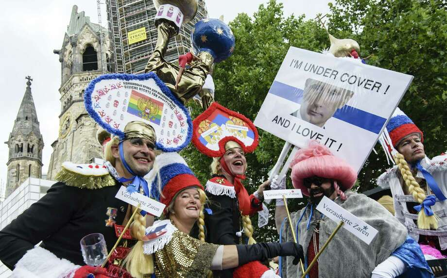 Berlin, GermanyParticipants wear hats featuring Russian church domes and hold a banner displaying a portrait of Russian President Vladimir Putin reading: 'I'm unter cover! And I love it!' during the Christopher Street Day (CSD) gay pride parade in front of Berlin's Memorial Church (Gedaechtniskirche) in Berlin, Germany on Saturday, June 21, 2014.   Photo: CLEMENS BILAN, AFP/Getty Images / AFP ImageForum