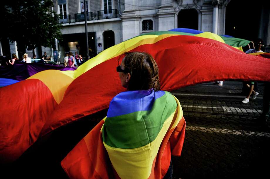 Lisbon, PortugalA woman drapped in a flag watches as giant rainbow flag passes during the Gay Pride Parade in Lisbon, Portugal on Saturday, June 21, 2014.  Photo: PATRICIA DE MELO MOREIRA, AFP/Getty Images / AFP ImageForum