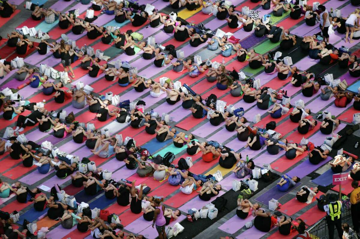 NEW YORK - JUNE 21: Over 8,000 people practice yoga as a salute to the sun at the 12th Annual Solstice in Times Square on June 21, 2014 in New York City. The day-long, free yoga event was sponsored by Athleta and the Times Square Alliance. (Photo by Yana Paskova/Getty Images) ORG XMIT: 498709945