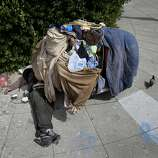 A homeless man sleeps beneath his cart on South Van Ness Avenue in San Francisco, Calif. It has been ten years since the original Care Not Cash program was adopted in San Francisco, Calif. Although thousands have been housed, the streets are still full of homeless people.