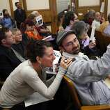 Jennifer Friedenbach, left, the director of the Coalition on Homelessness, confers with Bob Offer-Westort, the human rights organizer for the Coalition on Homelessness, during a board of supervisors meeting in San Francisco, Calif., Monday, January 23, 2012, to protest changes to two plazas in the Castro.