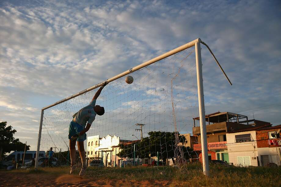 A young goalkeeper is beaten by a shot during a practice match at Serviluz favela in Fortaleza, Brazil.  Photo: Michael Steele, Getty Images