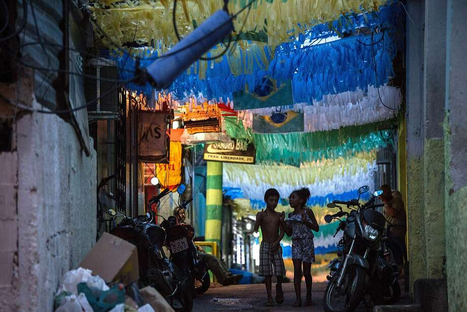 Two children walk along a street decorated in the Brazilian national colours in Rocinha favela in Rio de Janeiro. Photo: Yasuyoshi Chiba, AFP/Getty Images
