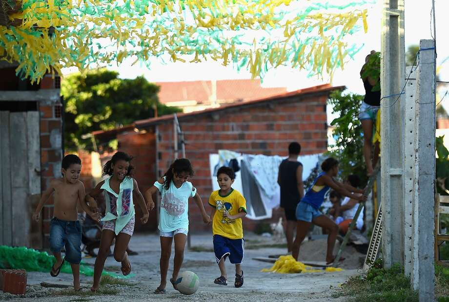 Children enjoy a game of soccer in the Serviluz Favela in Fortaleza. Photo: Jamie McDonald, Getty Images