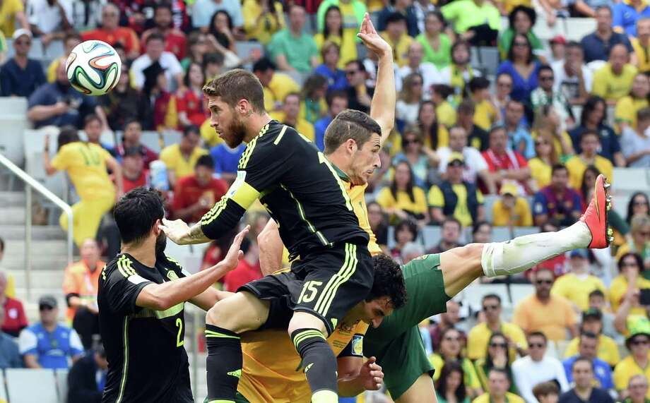 (FromL) Spain's defender Raul Albiol, Spain's defender Sergio Ramos, Australia's forward Mathew Leckie and Australia's midfielder Mile Jedinak jump for the ball during a Group B football match between Australia and Spain at the Baixada Arena in Curitiba during the 2014 FIFA World Cup on June 23, 2014.  AFP PHOTO / WILLIAM WESTWILLIAM WEST/AFP/Getty Images Photo: WILLIAM WEST, AFP/Getty Images / WILLIAM WEST