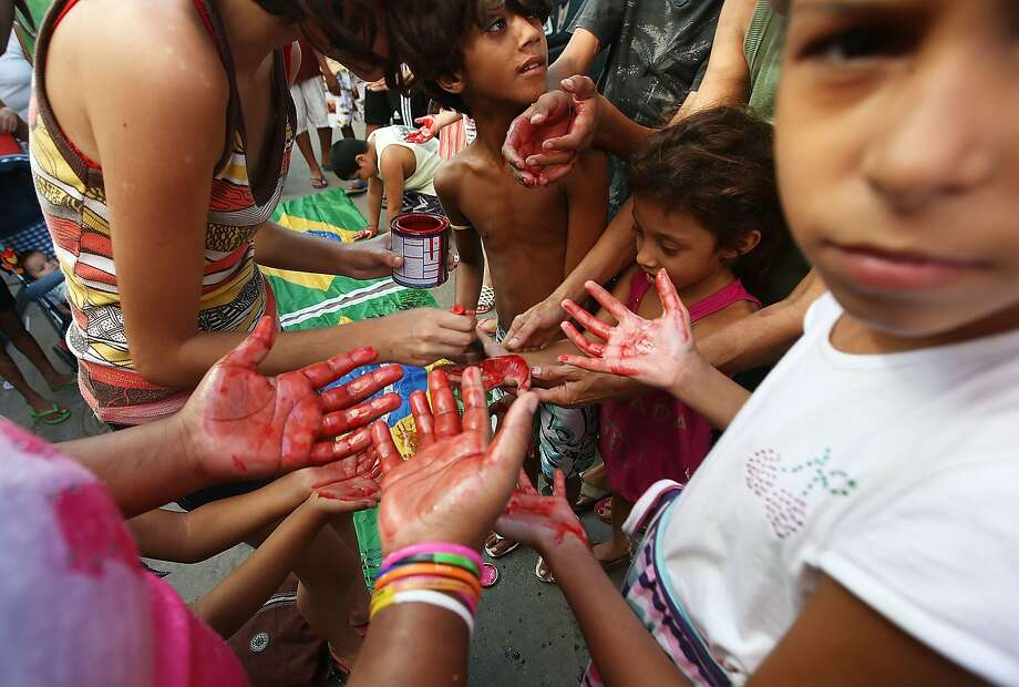 Young residents apply red paint to their hands, symbolizing the blood of Mare residents injured in deadly anti-World Cup protests. The favela is currently being occupied by the Brazilian army.  Photo: Mario Tama, Getty Images