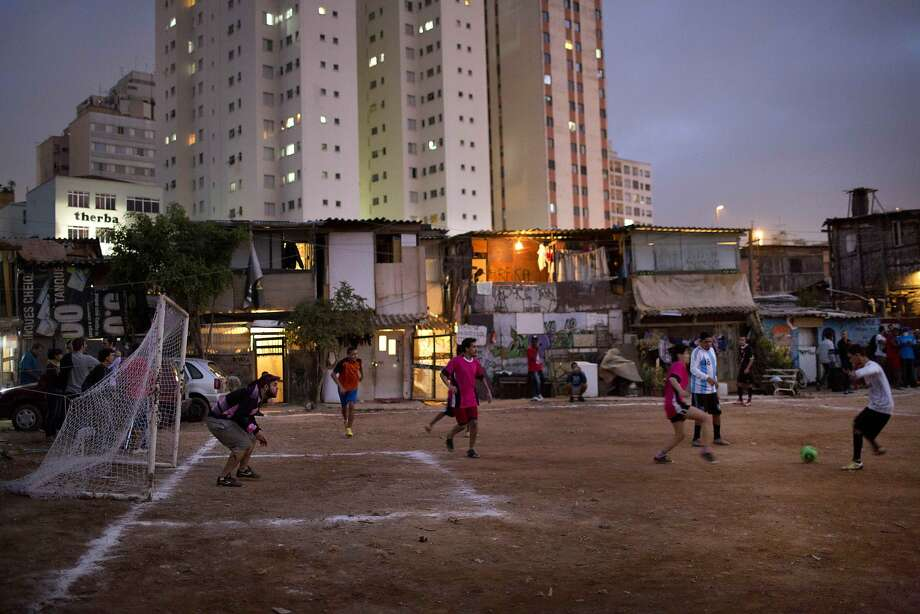"Residents of Favela Moinho play soccer during the ""Rebelde Cup."" Residents of the favela organized the soccer tournament in protest against the World Cup, claiming that the resources spent on the World Cup tournament would have been better spent in giving them access to potable water, electricity and a drainage sewer system.  Photo: Rodrigo Abd, Associated Press"