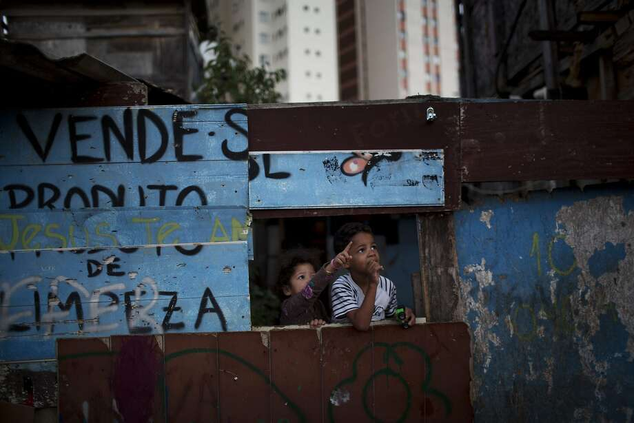 Children gather in a makeshift house as residents play a soccer match in Favela Moinho. Photo: Rodrigo Abd, Associated Press