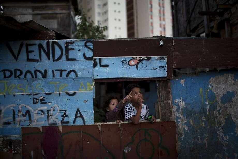 Children gather in a makeshift house as residents play a soccer match in Favela Moinho. Photo: Rodrigo Abd, Associated Press