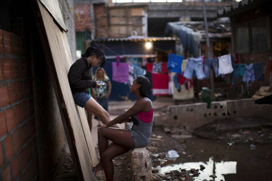 Young women gather near the soccer field in Favela Moinho in Sao Paulo, Brazil. Photo: Rodrigo Abd, Associated Press