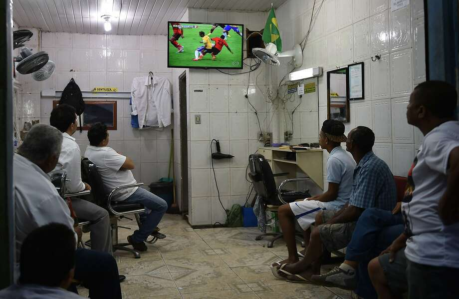 Brazilian fans watch a live broadcast of the match between Brazil and Mexico in Rocinha, the largest favela in Rio de Janeiro, on June 17. Photo: Yasuyoshi Chiba, AFP/Getty Images