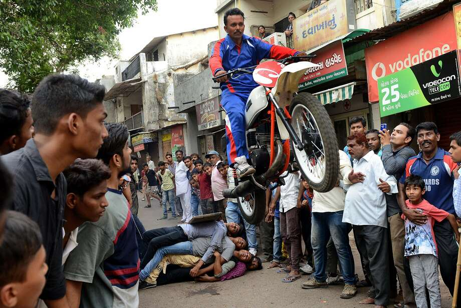 Kalpesh gets the glory, his assistants get sore ribs:Kalpesh Modi jumps his motorcycle off a human ramp while practicing for the Lord Jagannath Rath Yatra festival in Ahmedabad, India. Photo: Sam Panthaky, AFP/Getty Images